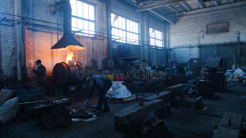 Iron and steel factory workers. Stock footage. Inside the factory of metal forms stock images