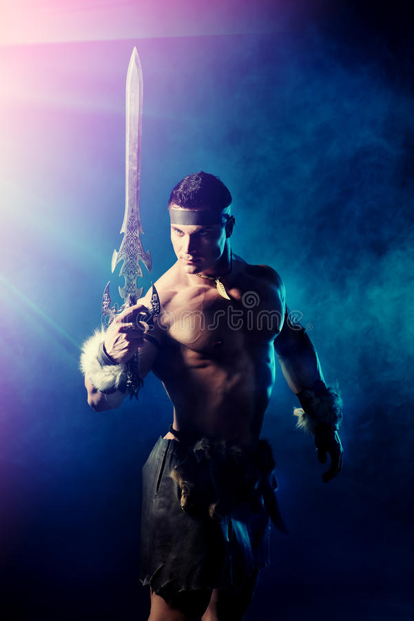 Iron sword. Portrait of a handsome muscular ancient warrior with a sword stock image