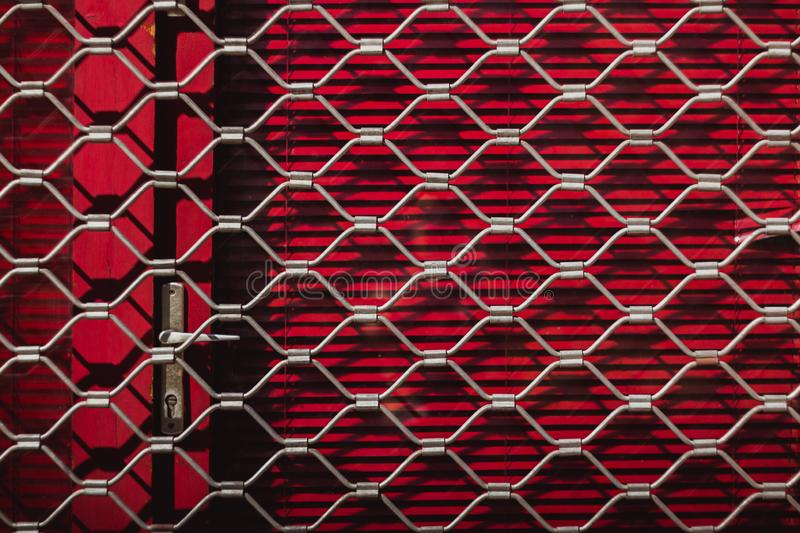 Iron texture of a steel grill on red shutters on the door. Red background. Outside royalty free stock images