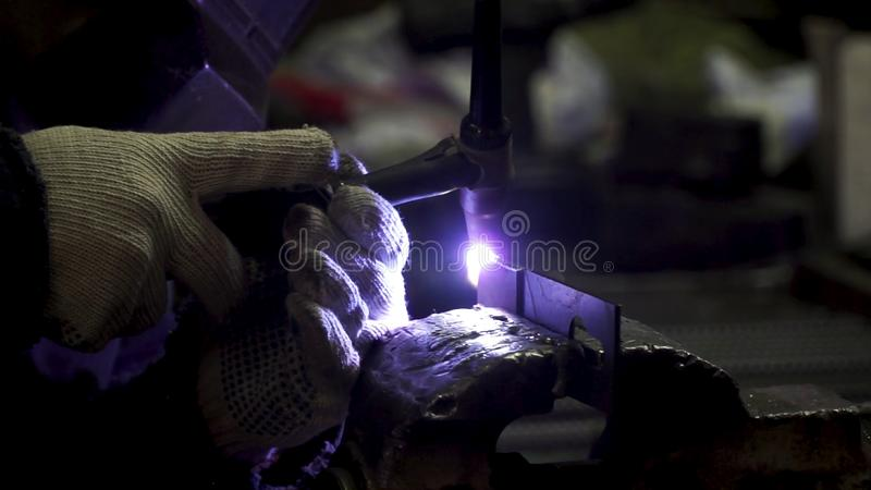 Iron welding with bright light and smoke at manufacturing. Clip. Industrial worker man at the factory welding close up. By arc stock photos