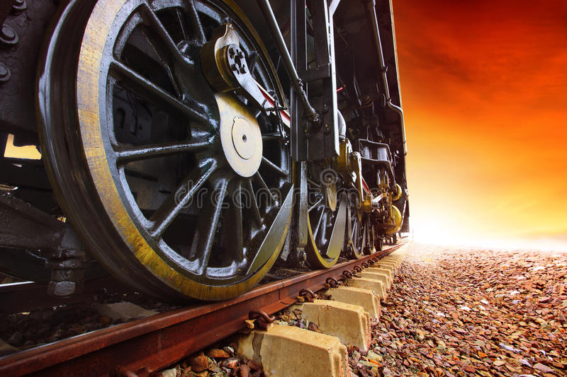Iron wheels of stream engine locomotive train on railways track. Perspective to golden light forward use for old and classic period land transport and retro stock images
