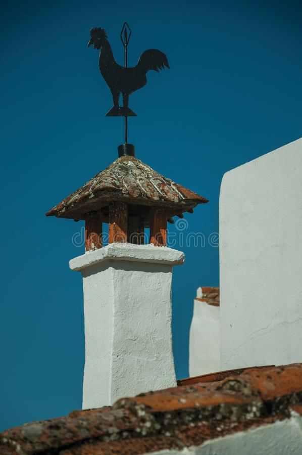 Iron wind vane over chimney on rooftop stock images