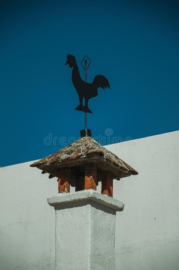 Iron wind vane over chimney on rooftop royalty free stock image