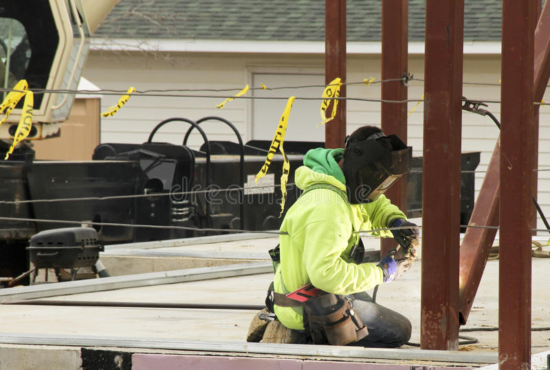 Iron worker welds beams. Iron worker strikes an arc as he welds beams together in the construction of a building stock photography