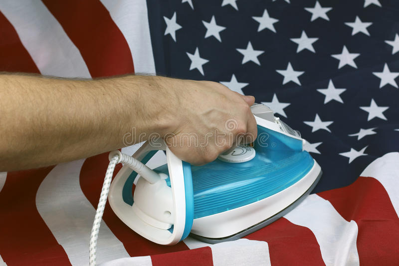 Ironed Crumpled US flag. Conceptual photography male hand with the included iron irons American Stripes royalty free stock image