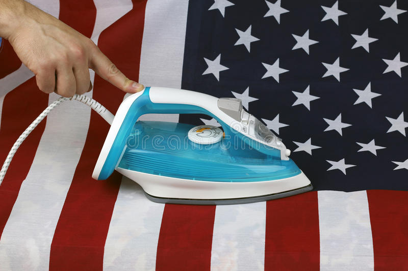 Ironed Crumpled US flag. Conceptual photography male hand with the included iron irons American Stripes stock images