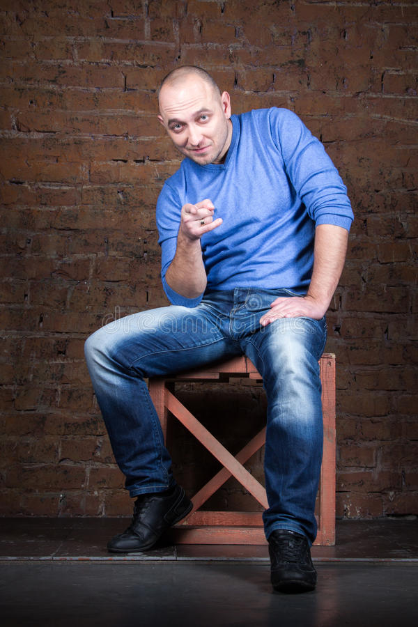 Ironic man sitting near the brick wall royalty free stock photo