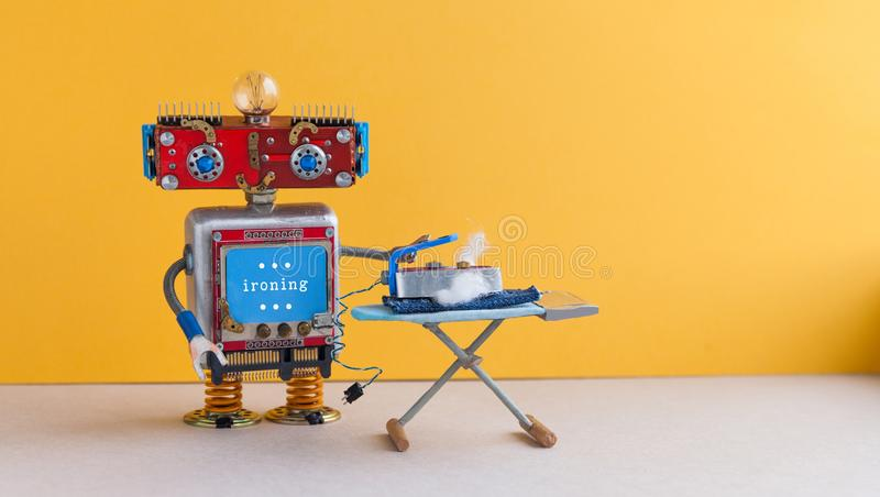 Ironing blue jeans with board. Robot housework helper with iron, yellow wall gray floor room interior. Creative design. Toys housework concept. Copy space royalty free stock images