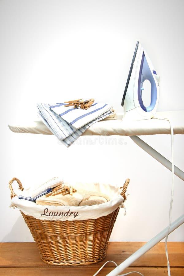 Ironing board with laundry. Against white background stock photo