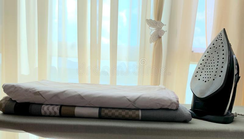 Ironing board, stack of sheets, iron. Household, ironing. Ironing board in gray, a stack of linen with a pattern, iron for ironing. Interior.n stock images