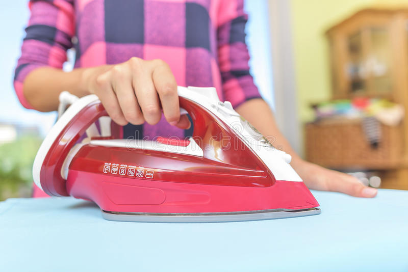 Ironing clothes on an board. Ironing clothes on an ironing board. Close-up stock images