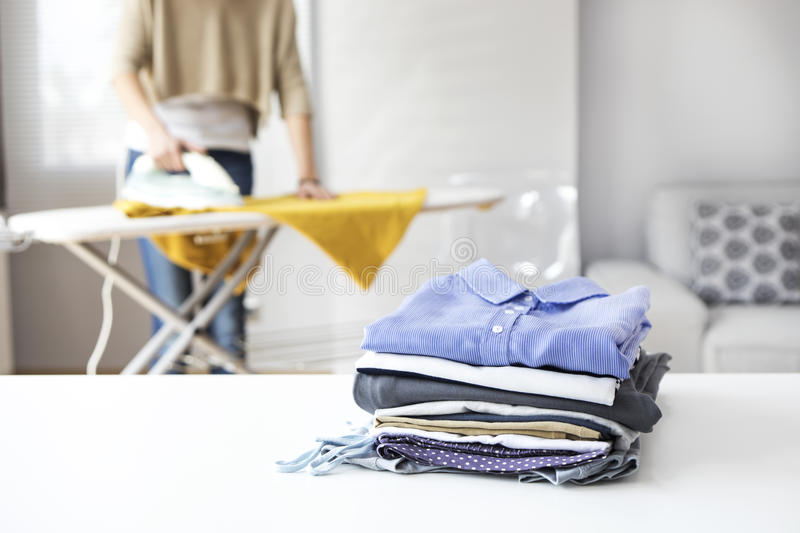 Ironing clothes on ironing board royalty free stock photo