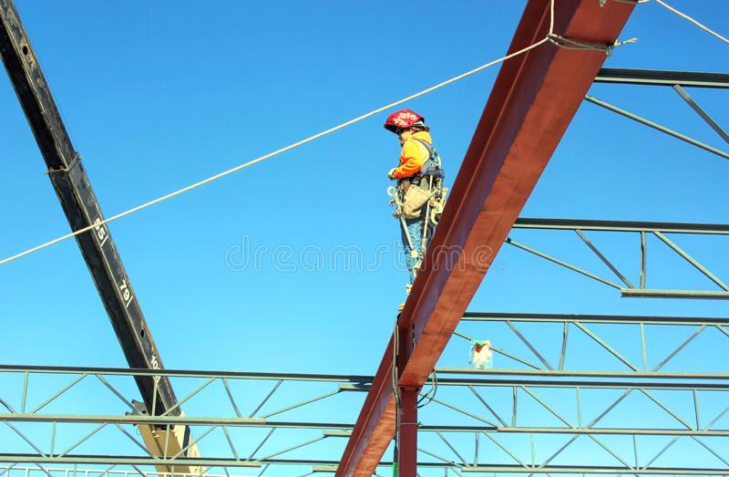 An Ironworker /Welder Awaits a Bar Joist. An ironworker / welder waits for his partner on the other end to swing a bar joist currently suspended by the crane royalty free stock image
