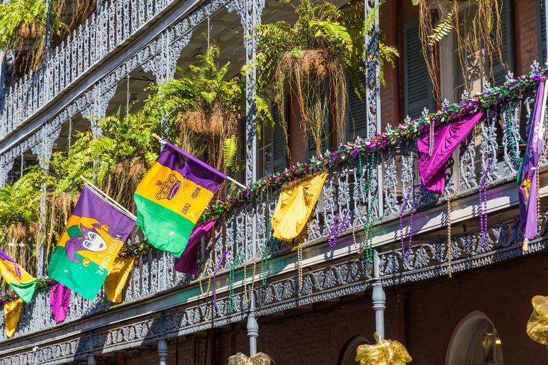 Ironworkgallerier på gatorna av den franska fjärdedelen dekorerade för Mardi Gras i New Orleans, Louisiana