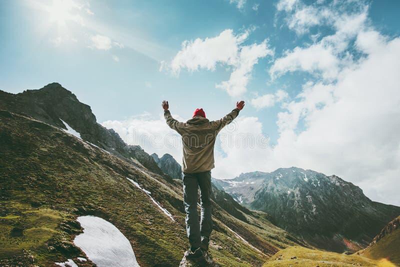 Irrar den lyckliga mannen lyftta händer som står på klippan, bergsikt royaltyfri foto