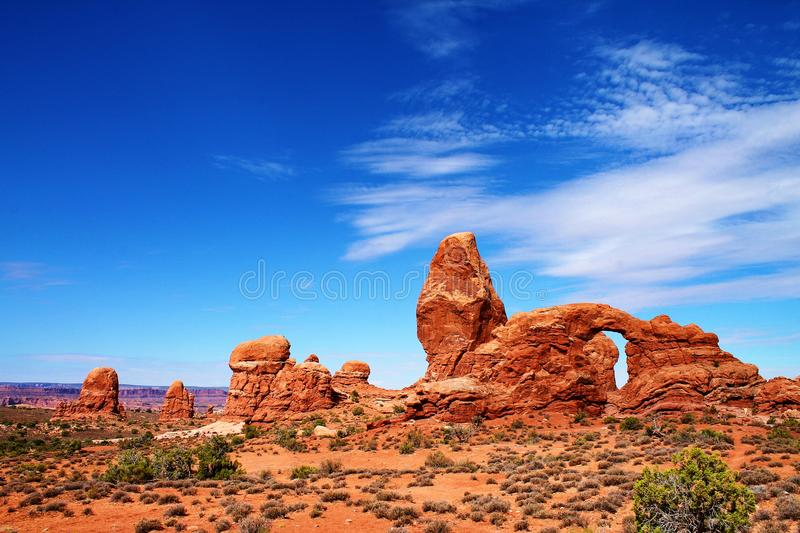 Irregular rock formations with pinnacles and arch, across a desert landscape in Utah stock photos