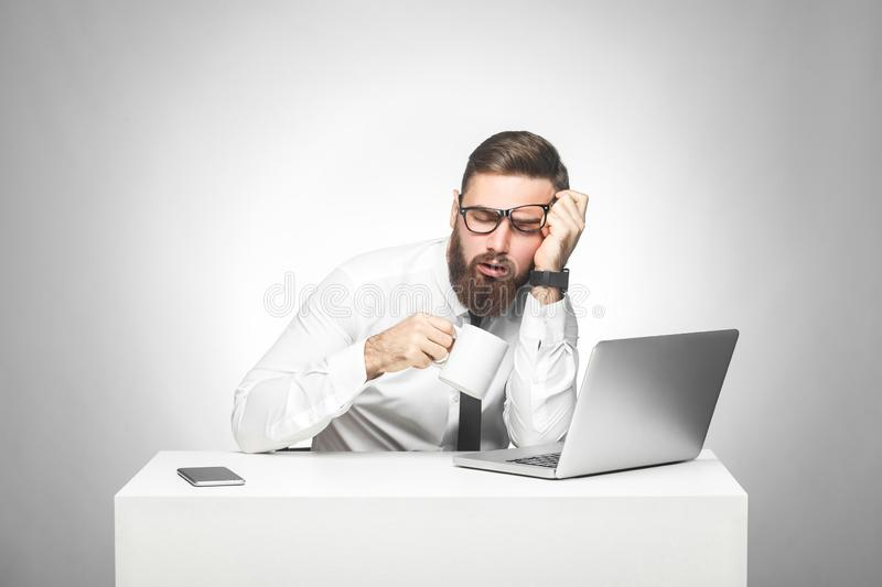 Irresponsible tired young manager in white shirt and black tie are sitting in office and trying not to sleep on the work, drink a royalty free stock photo
