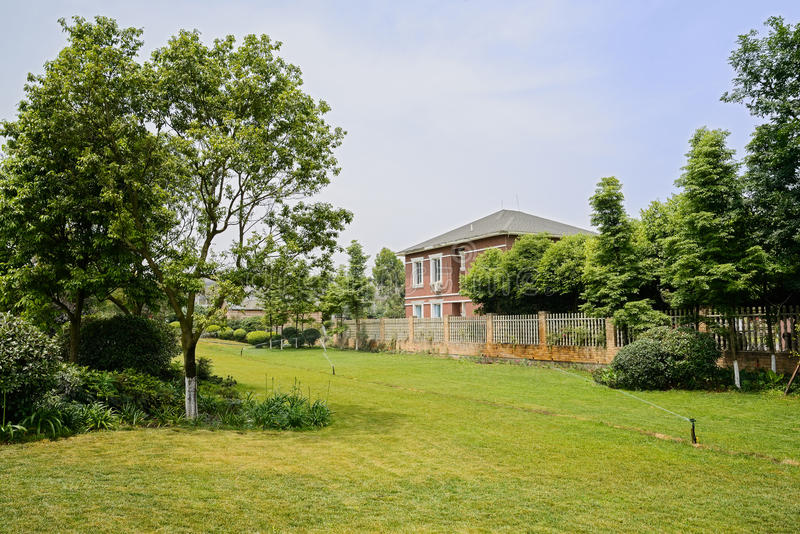 Irrigated lawn before fenced house in sunny summer stock images