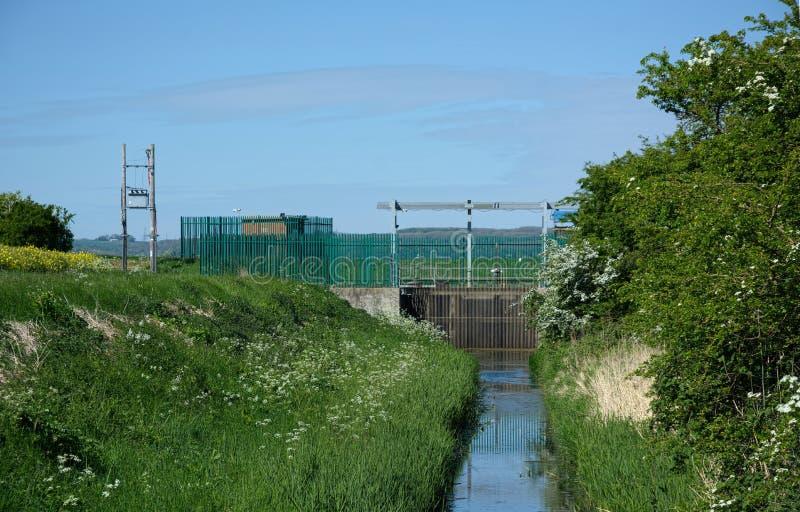 Irrigatiekanaal & sluispoort voor landbouwgrond stock afbeeldingen