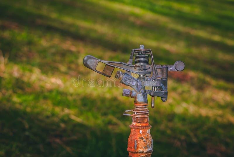 Irrigatiesproeier die aan een oude pijp wordt aangesloten royalty-vrije stock afbeeldingen