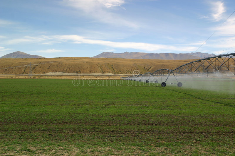 Irrigating Pastures. A Rolling Water Boom Irrigating The Crops stock photography