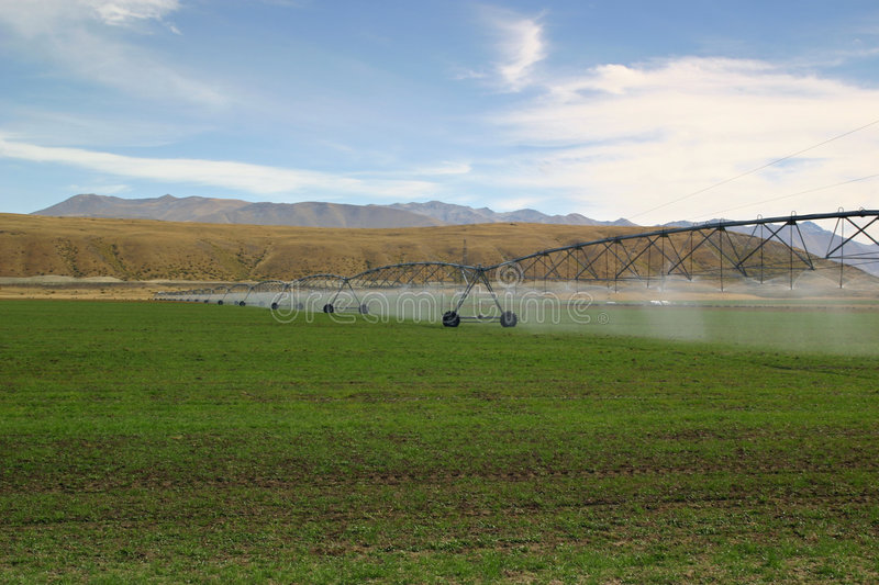 Irrigating Pastures. A Rolling Water Boom Irrigating The Crops stock images