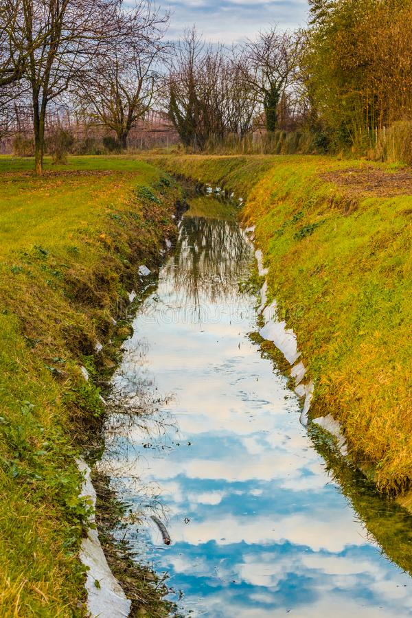 Irrigation canal in the countryside. Irrigation channel in the countryside of Emilia Romagna in Italy stock images
