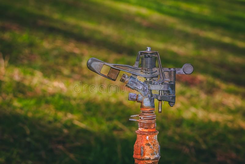Irrigation sprinkler connected to an old pipe royalty free stock images