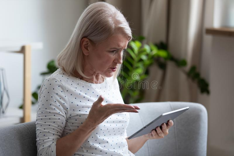 Irritated aged woman holding broken tablet having problems with gadget royalty free stock photo