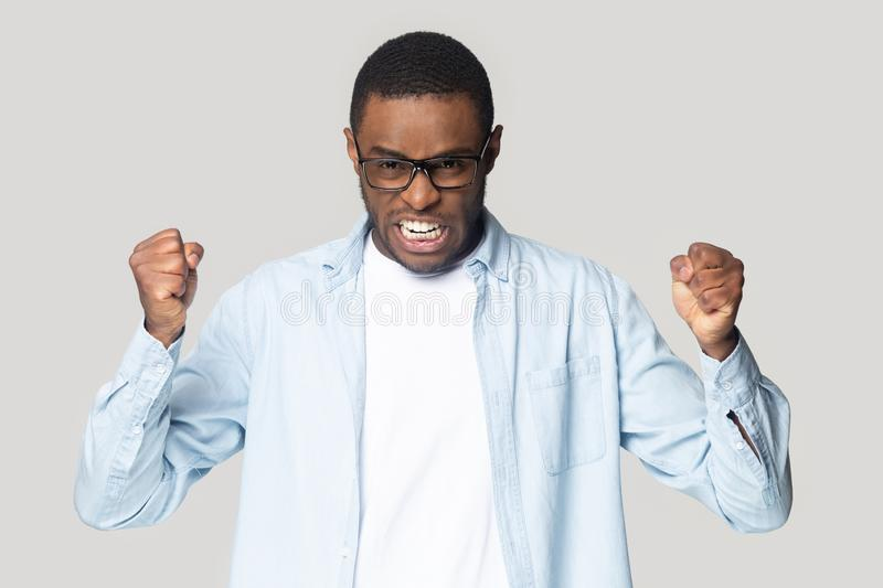 Irritated angry african american guy clenching both hands in fists. stock images
