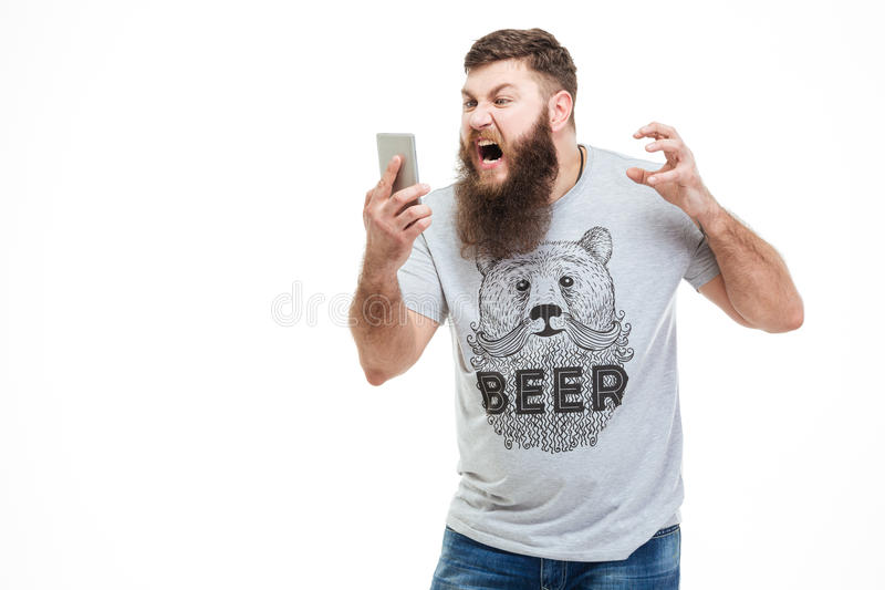 Irritated angry man with beard holding smartphone and shouting. Over white background royalty free stock photography