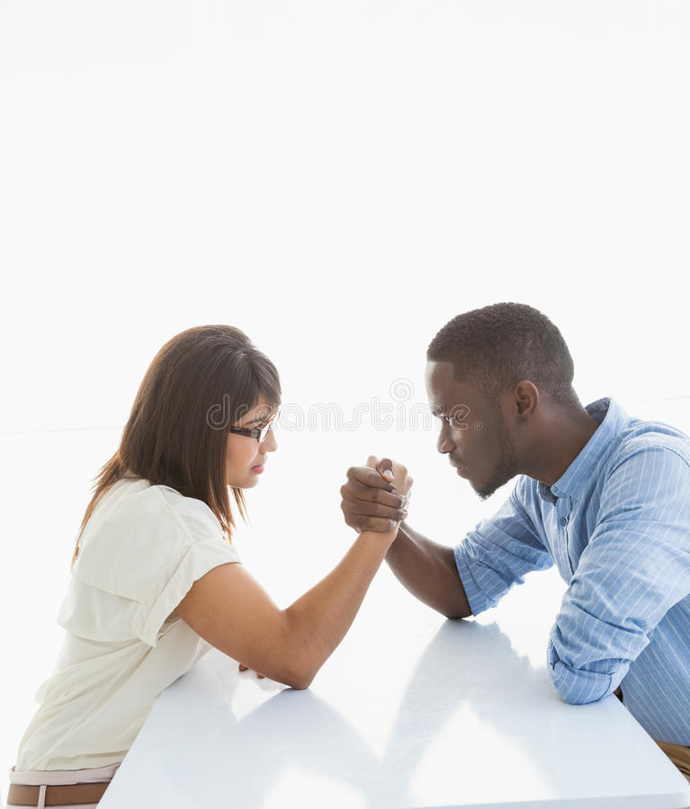 Irritated business couple arm wrestling at desk stock photography