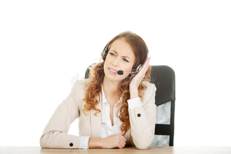 Irritated call center woman by a desk. royalty free stock photo