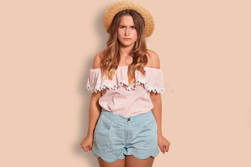 Irritated Caucasian girl looks with annoyance, keeps fists clenched, wears summer clothes, over studio background. Negati. Ve girlfriend annoyed with spoiled royalty free stock image
