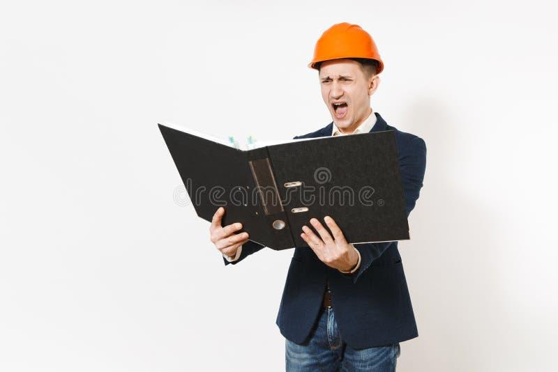 Irritated descontentó al hombre de negocios en el traje oscuro, casco anaranjado protector gritando en la carpeta negra para el d fotos de archivo libres de regalías