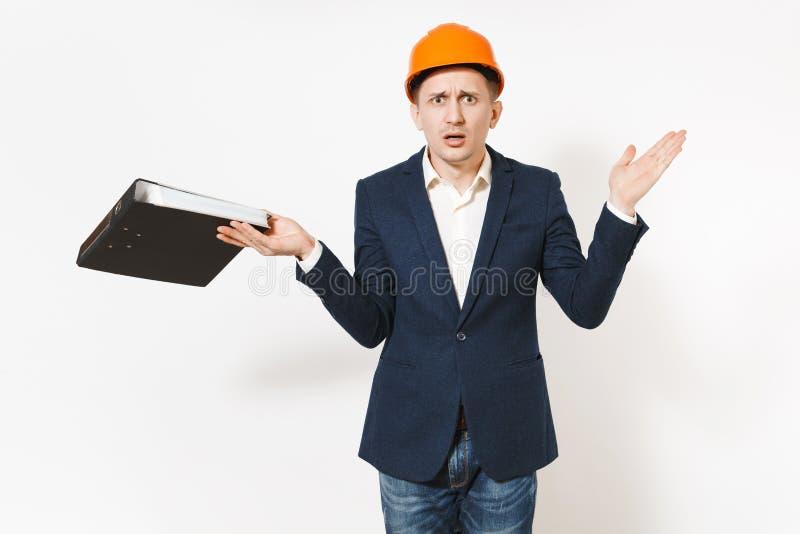 Irritated descontentó al hombre de negocios en el traje oscuro, casco de protección protector que sostenía la carpeta negra para  fotografía de archivo libre de regalías