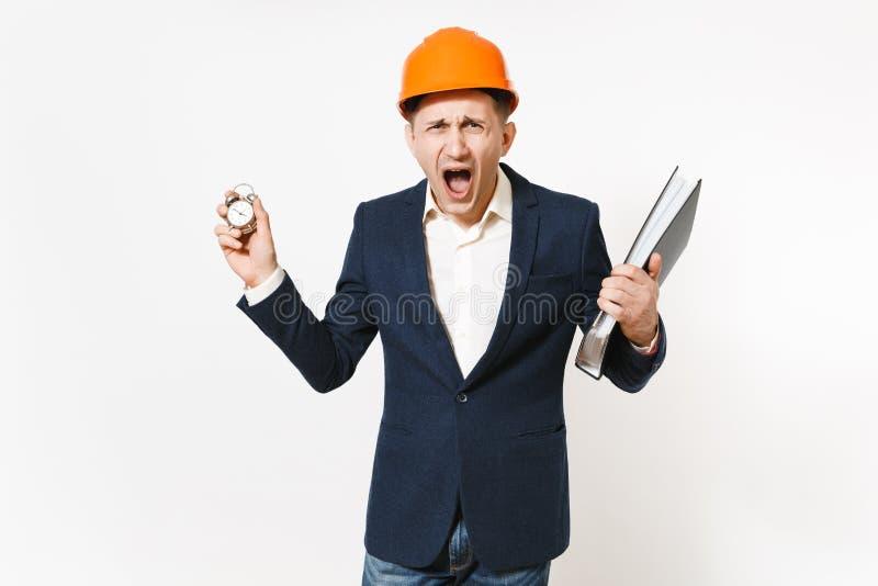 Irritated descontentó al hombre de negocios en el traje oscuro, casco protector de la construcción gritando y sosteniendo la carp imagen de archivo libre de regalías
