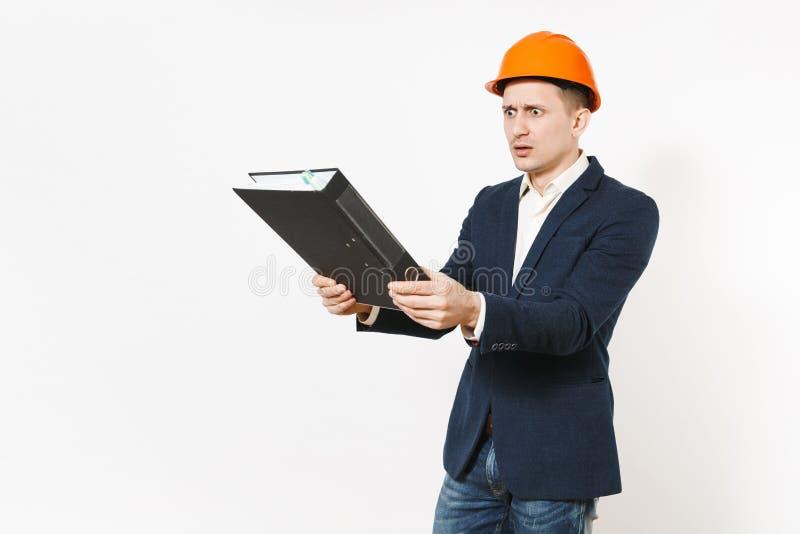 Irritated descontentó al hombre de negocios en el traje oscuro, casco protector de la construcción que sostenía la carpeta negra  fotos de archivo libres de regalías
