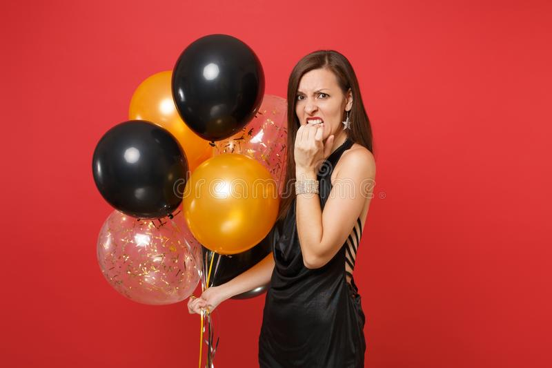 Irritated dissatisfied woman in black dress celebrate hold air balloons gnawing fingers, nails on hand isolated on red. Background. Valentine`s Day Happy New royalty free stock photo