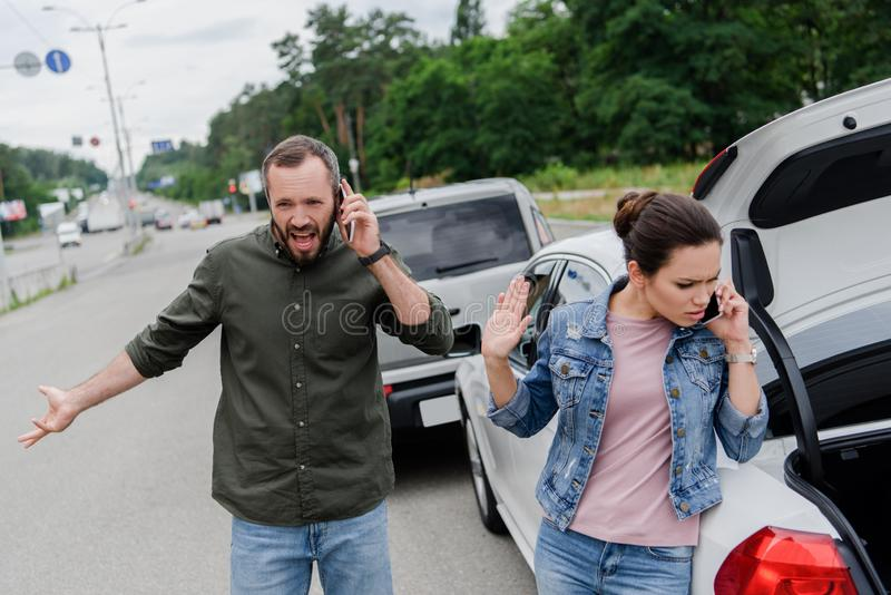 Irritated drivers talking by smartphones on road after. Car accident royalty free stock photos