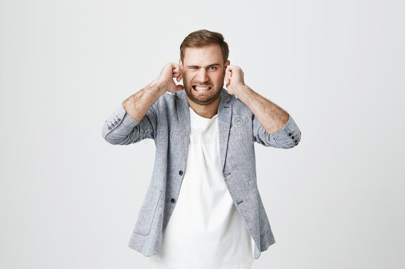 Irritated handsome bearded male with displeased facie expression, plugs ears, clenches teeth, expresses negativeness stock images