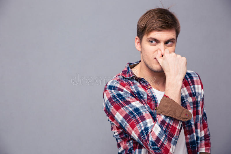 Irritated handsome young man in plaid shirt covered his nose. Because of bad smell over grey background stock photography