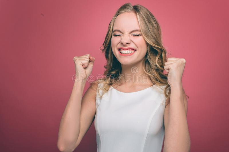 Irritated and mad young woman is getting crazy. She is upset. Girl has closed her eyes and holding her fists close to stock photos