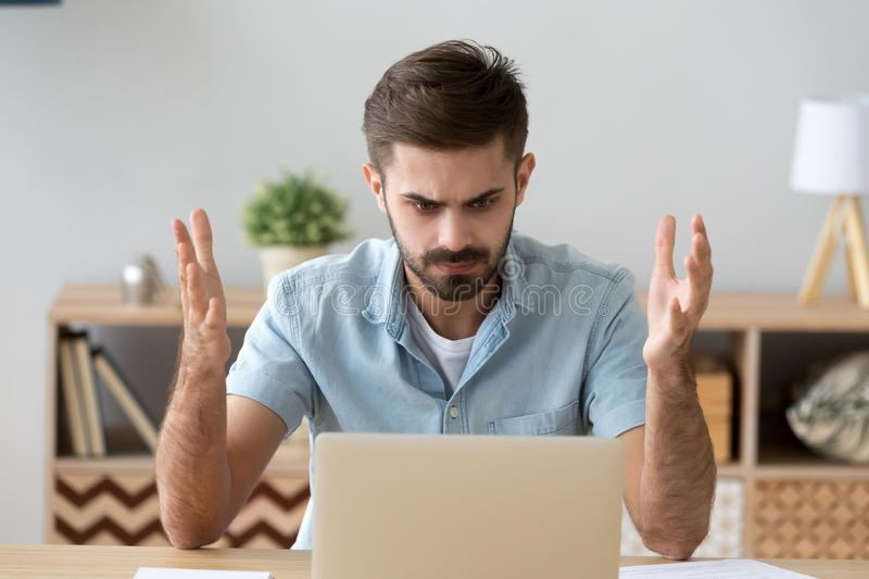 Irritated man looking at laptop screen sitting at the desk stock images
