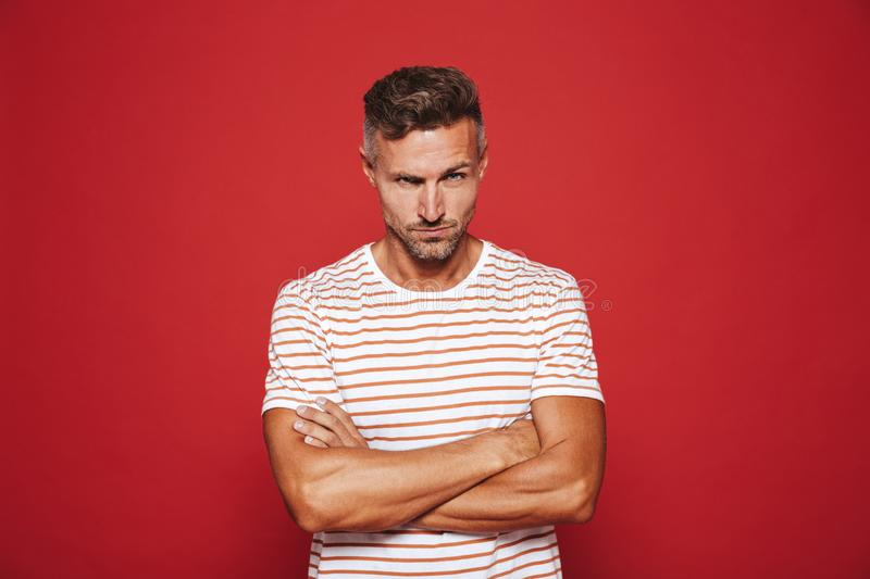 Irritated man 30s in striped t-shirt standing with arms crossed stock photography