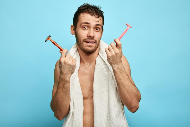 Irritated puzzled man going to shave beard, holds sharp two razors stock photo