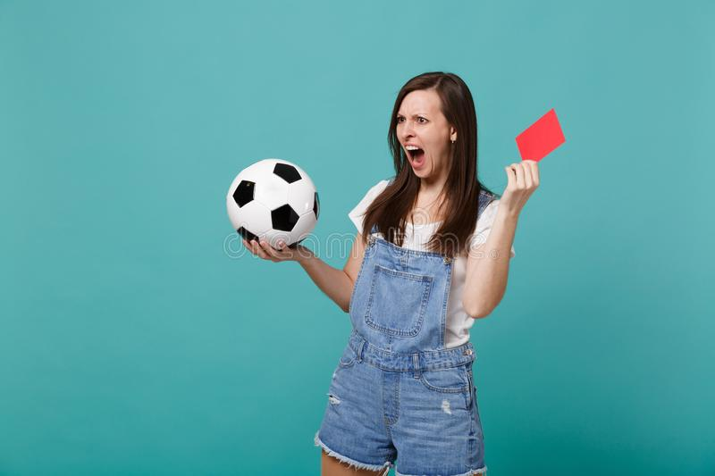 Irritated shocked young girl football fan support team with soccer ball, red card propose player retire from field. Isolated on blue turquoise background stock photo