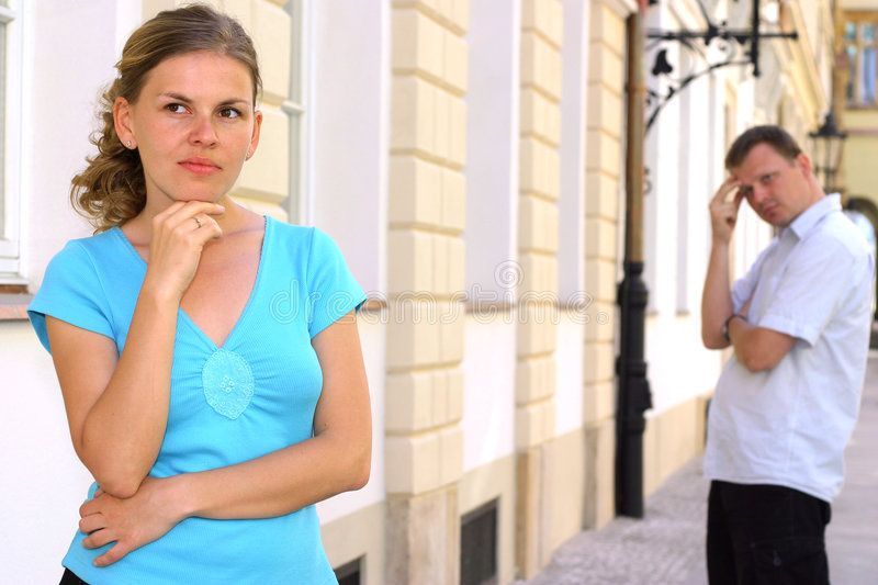 Irritated woman. And her man in the background royalty free stock image
