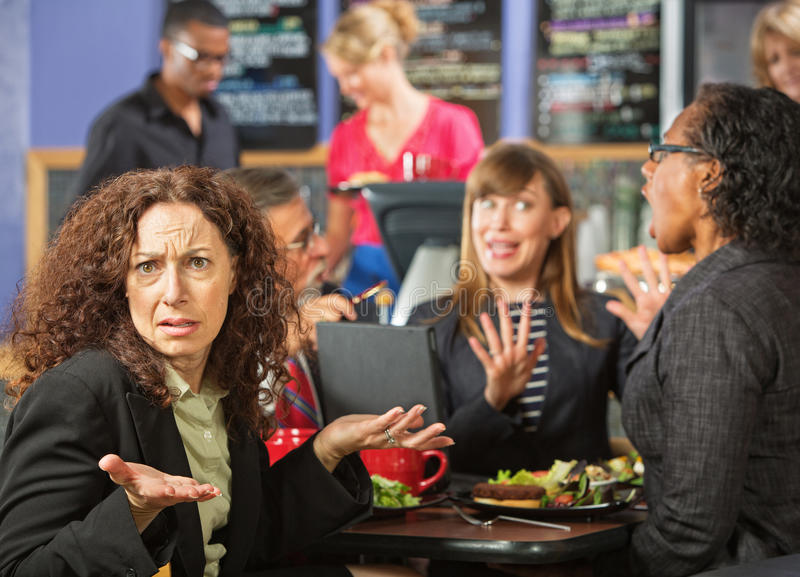 Irritated Woman in Cafe. Irritated business women with coworkers in cafeteria stock photography