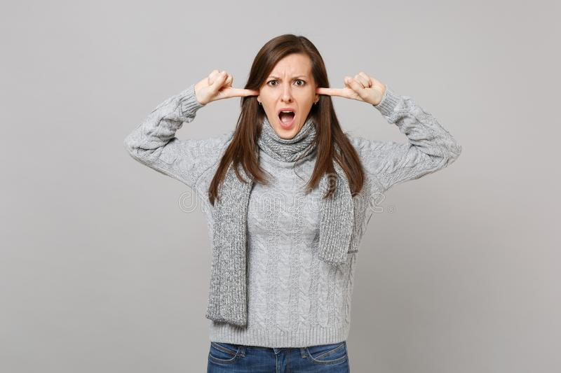 Irritated woman in gray sweater scarf covering ears with fingers keeping mouth wide open on grey background stock images